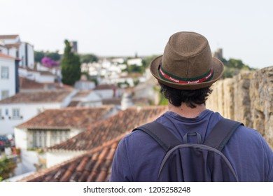 Obidos / Portugal - 08-05-2018: A boy with hat walks ona path of Obidos' s defensive medieval walls