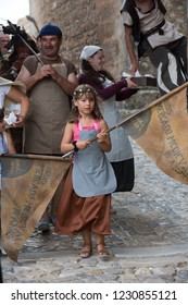 Obidos, Portugal - 23 July 2017: Medieval festival inside the old walled city of Obidos - girl with flag