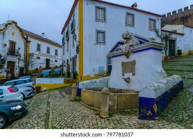 OBIDOS, PORTUGAL - DECEMBER 28, 2017: View of alleys in the old town, with local businesses, in Obidos, Portugal