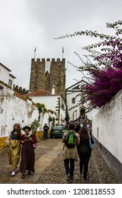 Obidos, Portugal - Oct 21, 2018: Tourists dressed ancient costumes on the narrow street of Obidos town.