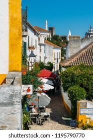Obidos, Portugal - Sept 25, 2018: Tourists and shops in the typical alleys of the ancient fortified village of Obidos, Oeste Leiria District, Portugal, Europe
