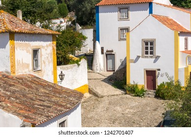 Obidos, Portugal, September 12, 2018: Houses of the town with blue and yellow property lines