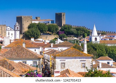 Obidos, Portugal, September 12, 2018: View from the gate side to the castle over houses roofs and mai stree torists flow