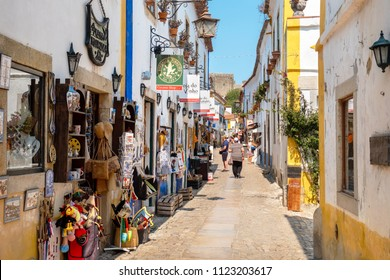 OBIDOS, PORTUGAL - SEPTEMBER 7, 2017: Tourist walking on cobbled street of medieval town