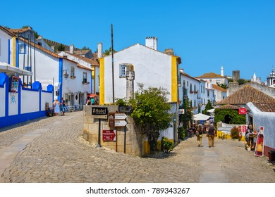 OBIDOS, PORTUGAL - SEPTEMBER 7, 2017: Tourist walking on cobbled streets of medieval town