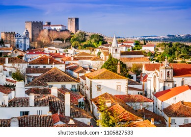Obidos, Portugal stonewalled city with medieval fortress, sunset light.