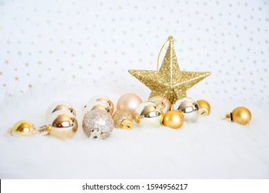 Object decorated, gold-yellow-gilter christmas ball on white fur with blackground burry star, merry chistmas and happy new year concept.