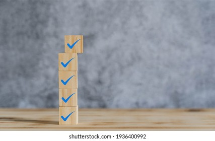 Object on the table of icon sign checklist on wooden block stacking same as step stair up on the blurred grey background, Business mark up concept. copy space for text. Clipboard and check marks
