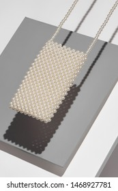 Object picture of crossbody pearls phone bag. The photo is taken on grey and white background. The bag is casting shadow on grey part of background.