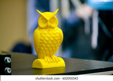 Object printed on a 3d printer close-up. Blurry background. Automatic three dimensional 3d printer performs plastic yellow colors modeling in laboratory. Progressive modern additive technology