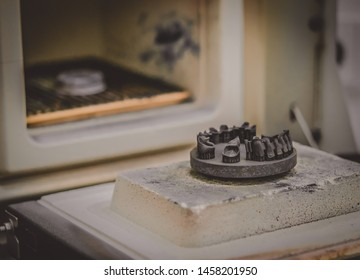 Object printed on metal 3d printer near the kiln for sintering after heat treatment synterization close-up. Dental crowns created in laser sintering machine. DMLS, SLM, SLS technology.