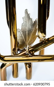 The object is a small golden tube designed as a home decor. Artificial metal maple leaf is placed on the golden tube for a decoration. This is not a building. / Golden tube design for home decor.