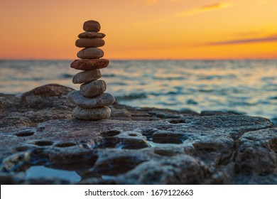 The object of the stones on the beach at sunset. Zen concept. Sunset. Silhouette of stones against the sunset sky