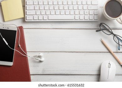 Objective business concept with white keyboard mobile phone notebook mouse sticky note pad eye glasses and coffee cup on the wooden table this have copy space