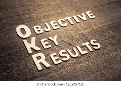 Objective Key Results (OKR) wood letters arraanged on wood background