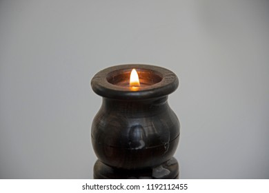 Objects - the burning candle in a wooden fine-molded candlestick