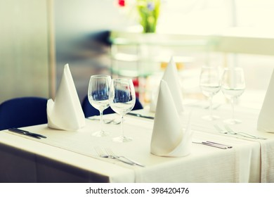 objects, dinnerware and holidays concept - close up of table setting with glasses, napkins and cutlery
