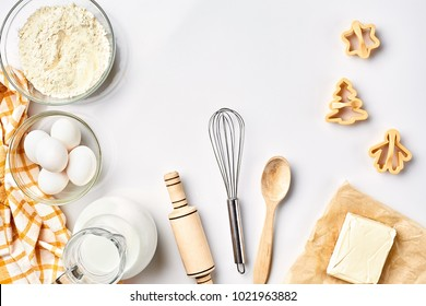 Objects and ingredients for baking, plastic molds for cookies on a white background. Flour, eggs, rolling pin, whisk, milk, butter, cream. Top view, space for text