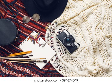 Objects top view  lifestyle essentials  of  artist girl or woman. Objects for painting, writing and sketching .Knitted sweater, bohemian stile. Retro vintage film camera,  art brushes.