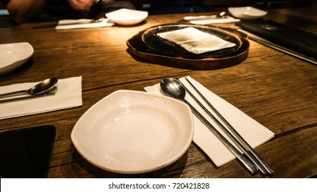 The objects of utensils, white plate, steel spoon and chop sticks with napkin put on the brown wooden table, ready for Asian dinner vintage style in the dim light for night time with family or friends