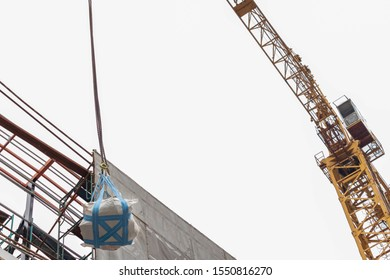 Objects wrapped in white cloth and blue belts are being lifted on top of the building with hooks of chains with yellow cranes.