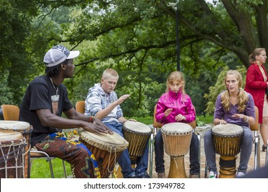 Oblegorek, Poland - July 31, 2011: Black musician from Africa demostrates how to play the drums to local children at free public workshops in Oblegorek on July 31, 2011.