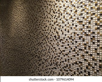 Oblique image of abstract pattern background from white,brown and black mosaic tile wall textured with reflection from lighting.