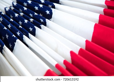 Oblique perspective of American patriotic fan or bunting made of folded fabric with red and white strips, beside blue star pattern, as a Veterans Day decoration