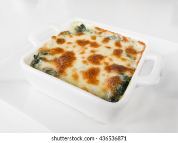 Oblique view of baked spinach and cheese on the white background.
