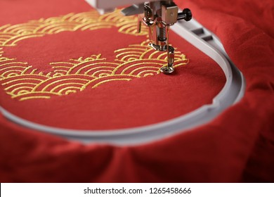 Oblique view on embroidery of traditional shell pattern framing pig outline with gold on red fabric by embroidery machine - chinese new year concept - view on stitching area with hoop and machine foot
