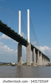 An oblique view of the Queen Elizabeth Bridge seen close up from the River Thames under a cloudy blue sky