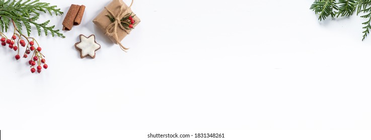 Oblong Christmas banner with small, wrapped gifts and other xmas decorations like spruce and fir twigs isolated on white background and lots of space for text.