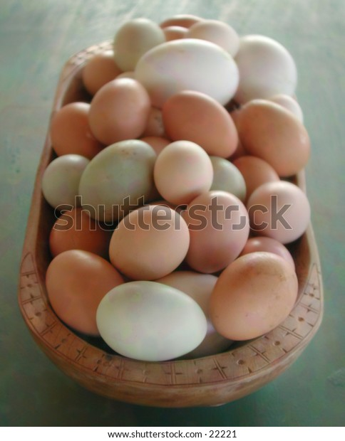 An oblong wood bowl of naturally colored eggs.