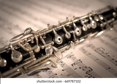 Oboe resting atop sheet music. The middle of the instrument appears in focus upon an open book of musical notes. The oboe has a black body with silver keys, made from grenadilla wood.