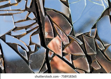 obscured image of a woman in broken glass reflection