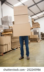 Obscured worker carrying boxes in the warehouse