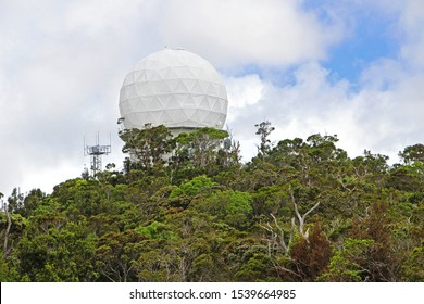 Observatory - the view on the dome, green hill covered with jungle trees, blue cloudy sky in the background. Kauai, Hawaii.