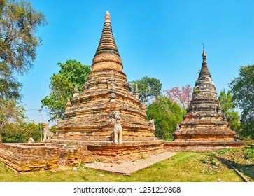 Observe the archaeological site of Daw Gyan pagoda with relief stupas, decorated with sculptures of chinthe (leogryphs) and topped with hti umbrellas, Ava (Inwa), Myanmar.