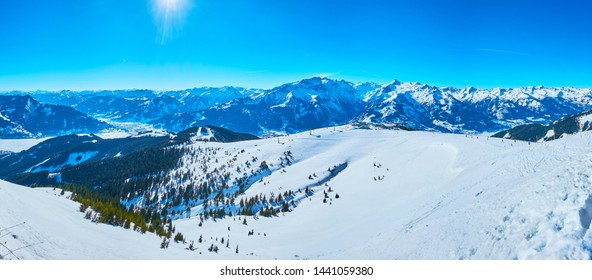 Observe the gentle snowy slopes of Schmitten mount with comfortable ski pistes and snowshoe routes, spruce forests and sharp rocks, Zell am See, Austria