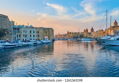 Observe the medieval cities of Senglea and Birgu, divided by waters of Vittoiosa marina, the shore of Birgu is lighted with last sunset rays, Malta.
