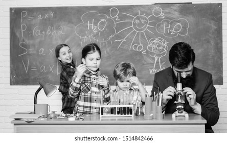 Observe reaction. Science is always the solution. School chemistry experiment. Explaining chemistry to kids. Fascinating chemistry lesson. Man bearded teacher and pupils with test tubes in classroom.