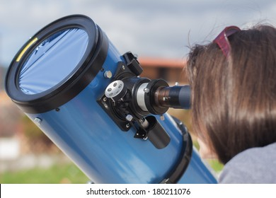 Observing the Sun through a telescope and a special filter to reduce sunlight. Watching a sun through a telescope without a filter can result in a permanent eye damage!