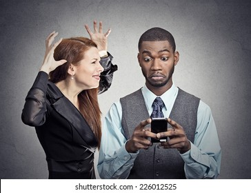 Obsessed with phone work. Attractive woman angry with handsome man who ignores her looking at smart phone reading texting isolated grey wall background. Phone addiction mania concept. Face expression