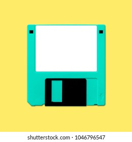 Obsolete 3.5 inch computer diskette, isolated and presented in punchy pastel colors with a blank white customizable label. Theme of early digital storage media for factual work and creative design