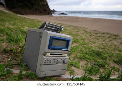 Obsolete cassette player sits abandoned on a sandy beach