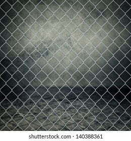 Obsolete gray grunge concrete room closed with chain link fence.