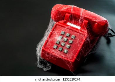 Obsolete technology and abandoned telephone concept with a vintage phone covered in spider webs isolated on black background with copy space
