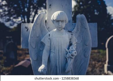 Obsolete white angel statue of tombstone cross in sunlight on cemetery of Dublin