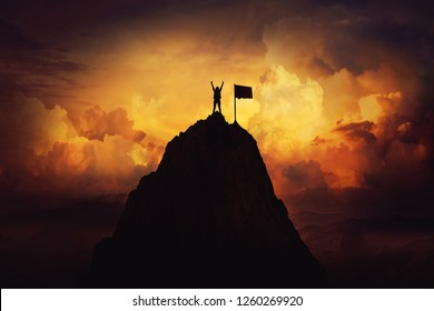 Obstacle overcome as a woman raise hands up on the top of a mountain reaching the finish flag. Celebrate victory and success over sunset background. Goal achievement symbol.