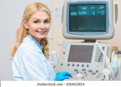 obstetrician gynecologist sitting at ultrasonic scanner and looking at camera